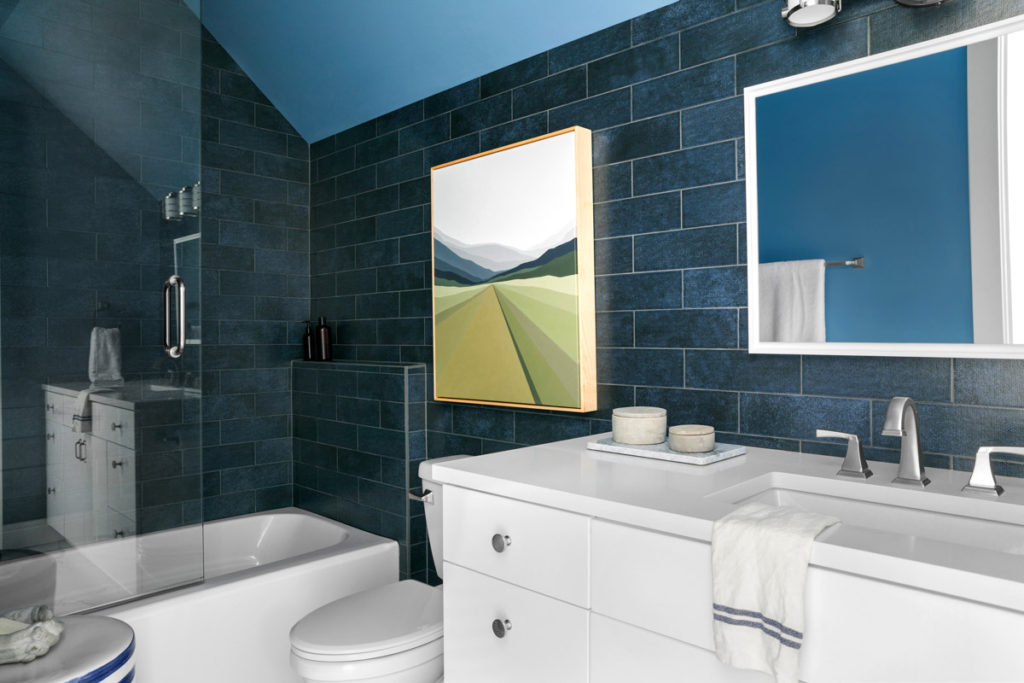 hgtv dream home bathroom with navy blue subway tile, painting, and mirror on wall and white vanity