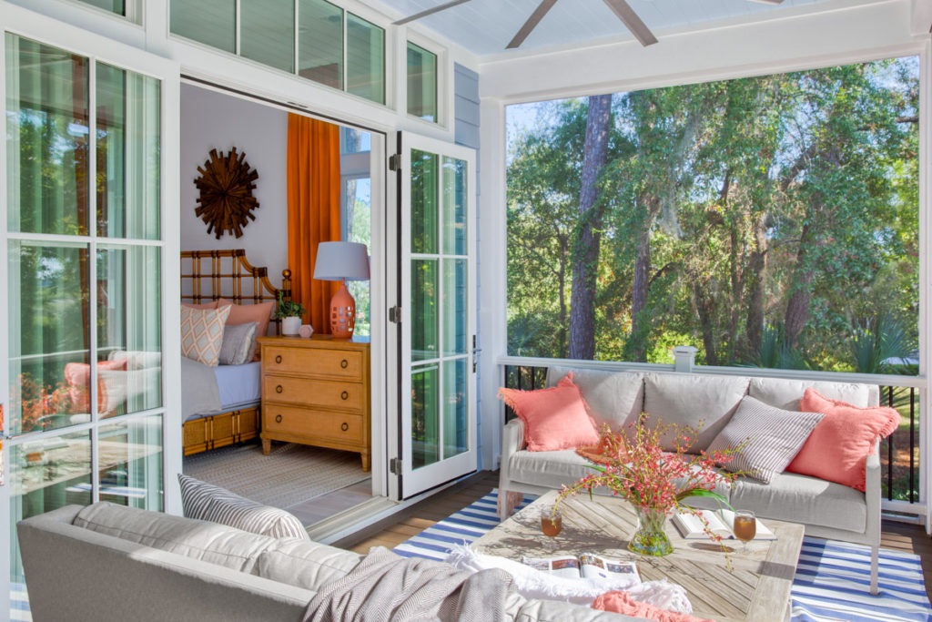 covered screen porch with glass doors leading to bedroom and taupe seating with coral pillows