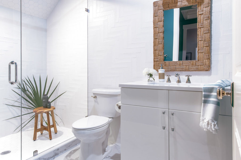 hgtv dream home bathroom with white chevron subway tile on walls, white vanity, woven framed mirror and teak stool ing shower with plant