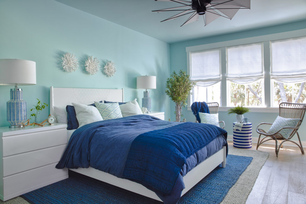 A turquoise walled bedroom with a bed with blue bedding and white headboard and side table