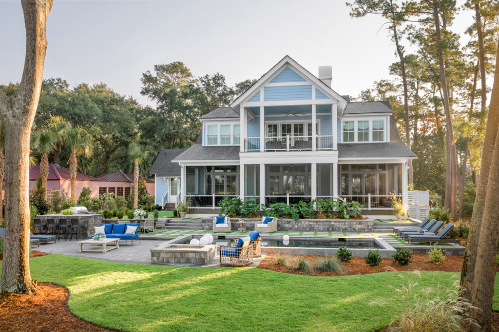 A large lawn with pool and outdoor fire pit behind a blue house that was the hgtv dream home 2020